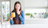 Beautiful Asian woman drinking a glass of fresh orange juice cover mouth with hand shocked with sham poster