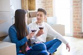 Young asian couple sitting on the floor of new apartment arround cardboard boxes, smiling drinking a poster