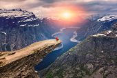 Norway, A woman sits on the mountains cliff edge of Trolltunga throning over Ringedalsvatnet  watch poster