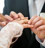 mans hand putting a wedding ring on the brides finger