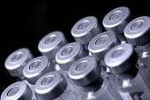 image of medical supplies  - glass vaccine phials on a black background - JPG