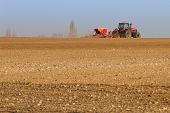 stock photo of cultivator-harrow  - Agriculture tractor sowing seeds and cultivating field  - JPG