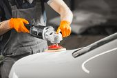 Worker Polished White Car With Orbital Polisher In Auto Repair Shop, Close-up. Vehicle Detailing. poster