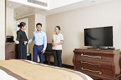 Asian Manager Of The Hotel Together With Maid Meeting The Businessman As Guest Of The Hotel And Show poster