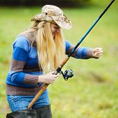 image of fisherwomen  - beautiful blond girl fishing in pond at autumn - JPG