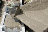 picture of hand-barrow  - Closeup of mason hand pouring out mortar into concrete shuttering blocks from wheel - JPG
