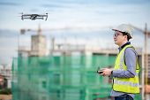 Asian Engineer Man Flying Drone Over Construction Site. Male Worker Using Unmanned Aerial Vehicle (u poster