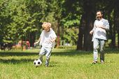 Father And Adorable Son Playing Football In Park During Daytime poster
