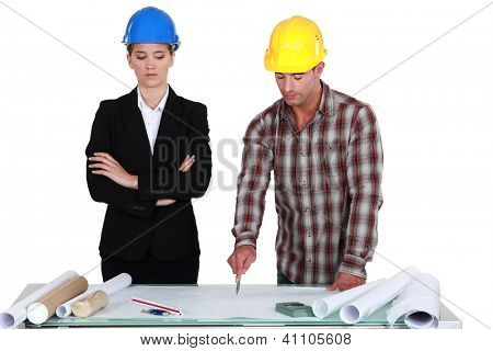 Tradesman pointing out an error to an engineer