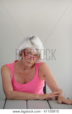 Sad middle-aged lady sat at a table