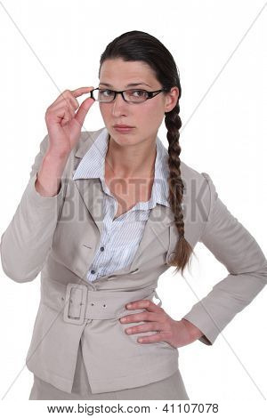 Stern businesswoman touching glasses