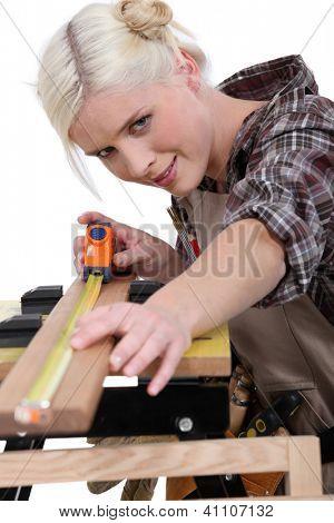 A female carpenter measuring.