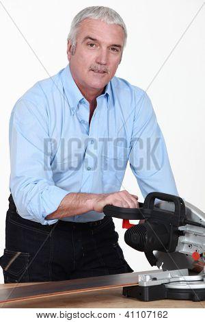 Man cutting parquet slat