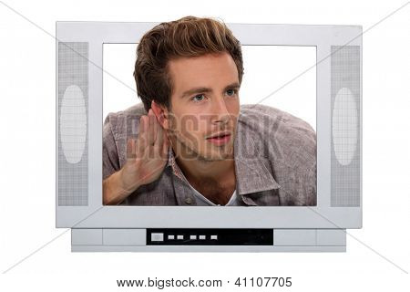 young man through a TV screen listening something carefully