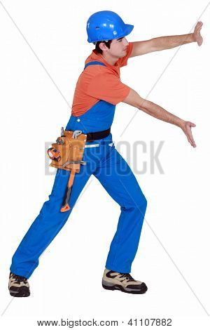 Tradesman pushing an invisible wall