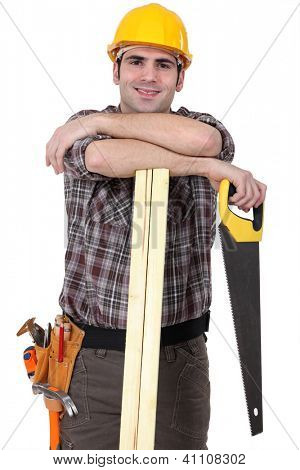 Carpenter with wood slats and saw