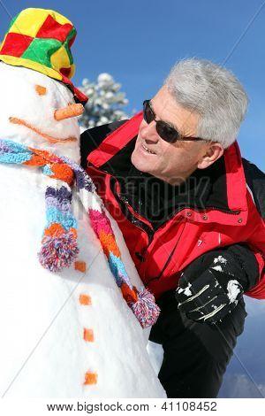 Senior man with a snowman
