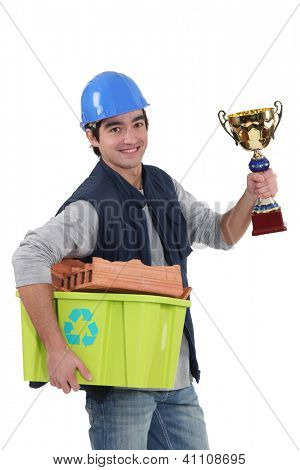 A manual worker with a trophy and a recycling basket.