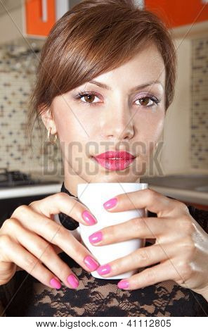 happy brunette in cafe at little table with cup of coffee