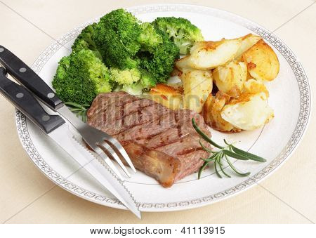 Grilled striploin steak served with crushed garlic potatoes and boiled broccoli