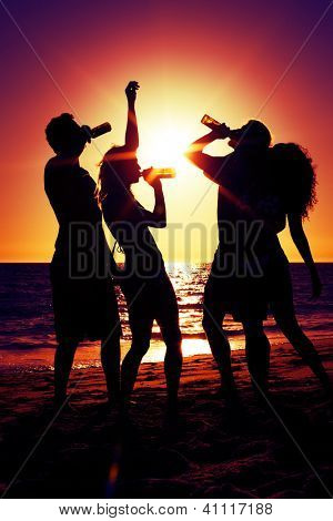 People (two couples) on the beach having a party, drinking and having a lot of fun in the sunset (only silhouette to be seen, people having bottles in their hands with the sun shining through)