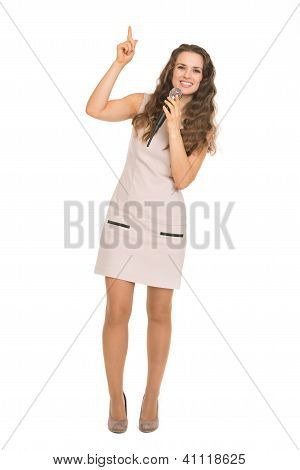 Happy Young Woman With Microphone Pointing Up On Copy Space