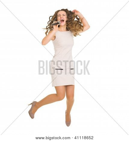 Happy Young Woman Jumping And Singing With Microphone