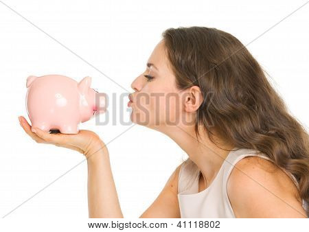Young Woman Kissing Piggy Bank