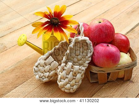 Summer Still Life With Decorative Sandals Made Of Bark And Small Basket Of Apples On A Wooden Table