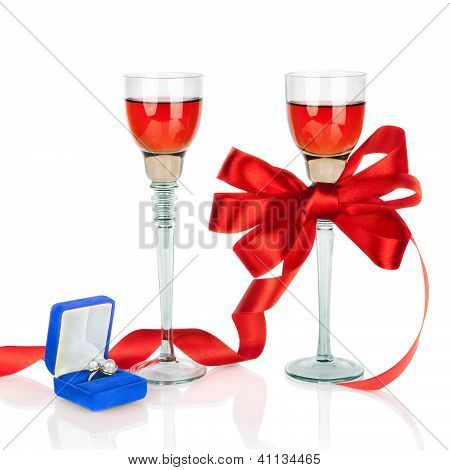 Wine In Two Wineglasses With Red Satin  Bow And Wedding Rings In Blue Gift Box Isolated On White Bac