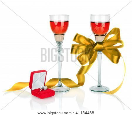 Wine In Two Wineglasses With Golden Satin  Bow And Wedding Rings In Red Gift Box Isolated On White B
