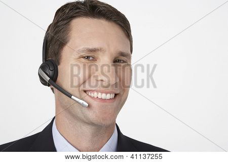 Closeup portrait of happy male telephone operator over white background