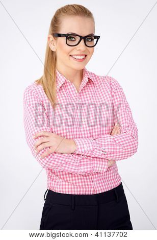 Portrait of a happy blonde geek girl in pink shirt and glasses