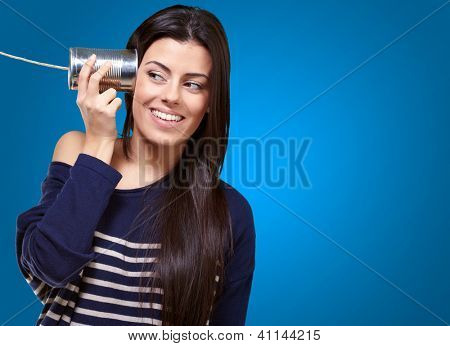 Female Holding A Metal Tin As A Telephone On A Blue Background