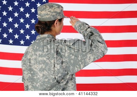 Closeup of an American Female Soldier in combat uniform saluting a flag. Seen from behind horizontal format with the flag filling the frame.