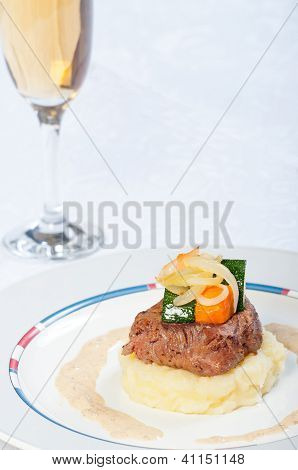 seared pan beef tenderloin with buttered vegetables and mashed potato on a side