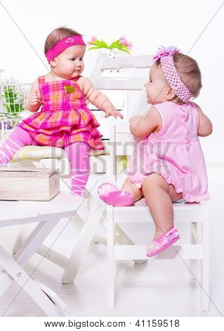 Two baby friends in festive dresses