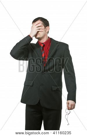 Businessman covers his eyes