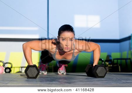 Gym woman push-up strength pushup exercise with dumbbell in a workout