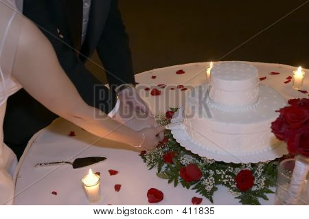 Bride And Groom Cut Wedding Cake By Candlelight