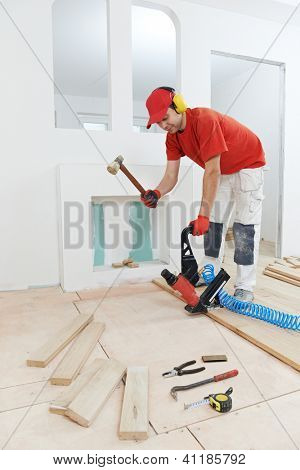 carpenter worker installing wood floor parquet board during flooring work with hammer
