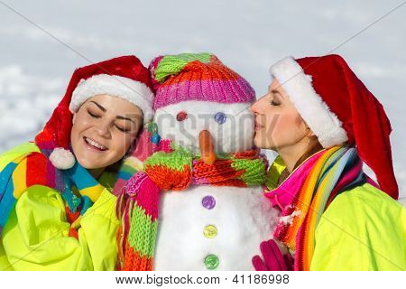 Side view of two girls kissing snowman outdoor on a warm winter day