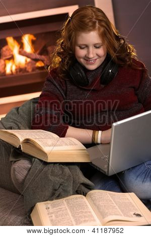 Redhead teenager girl learning at home with books and laptop, happy smile.