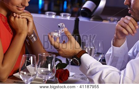 Romantic dinner with engagement ring. Young man proposing to woman.