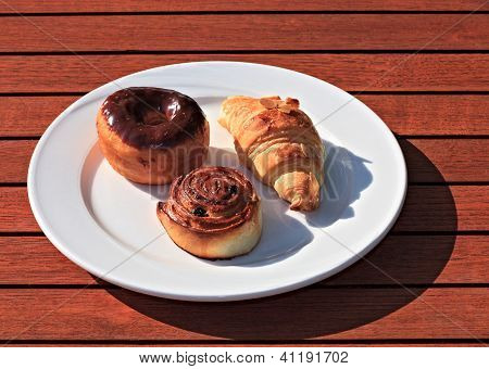 Croissant, Donut In Chocolate And Roll With Raisin