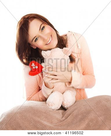 Picture of pretty woman with soft bear toy in bed, sweet young lady received gift for Valentine day, lovely brunette teen girl with romantic present isolated on white background, love concept