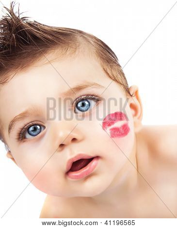Picture of small pretty kid with red lipstick kiss on the cheek, closeup portrait of cute baby boy isolated on white background, curious toddler with open mouth looking in the camera, Valentines day