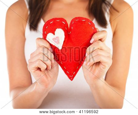 Picture of brunette woman holding red soft toy heart-shaped in hands, beautiful handmade present for Valentine day, romantic holiday, affection feelings, health care and medicine, love concept