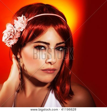 Photo of beautiful woman with red hair and stylish makeup isolated on red background, sexy woman wearing fashionable pink accessories on head, Valentine day, beauty and passion concept