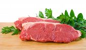 image of porterhouse steak  - Two raw porterhouse steaks on a wooden chopping board with herbs - JPG